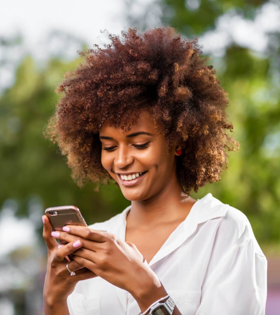 female smiling while checking her phone