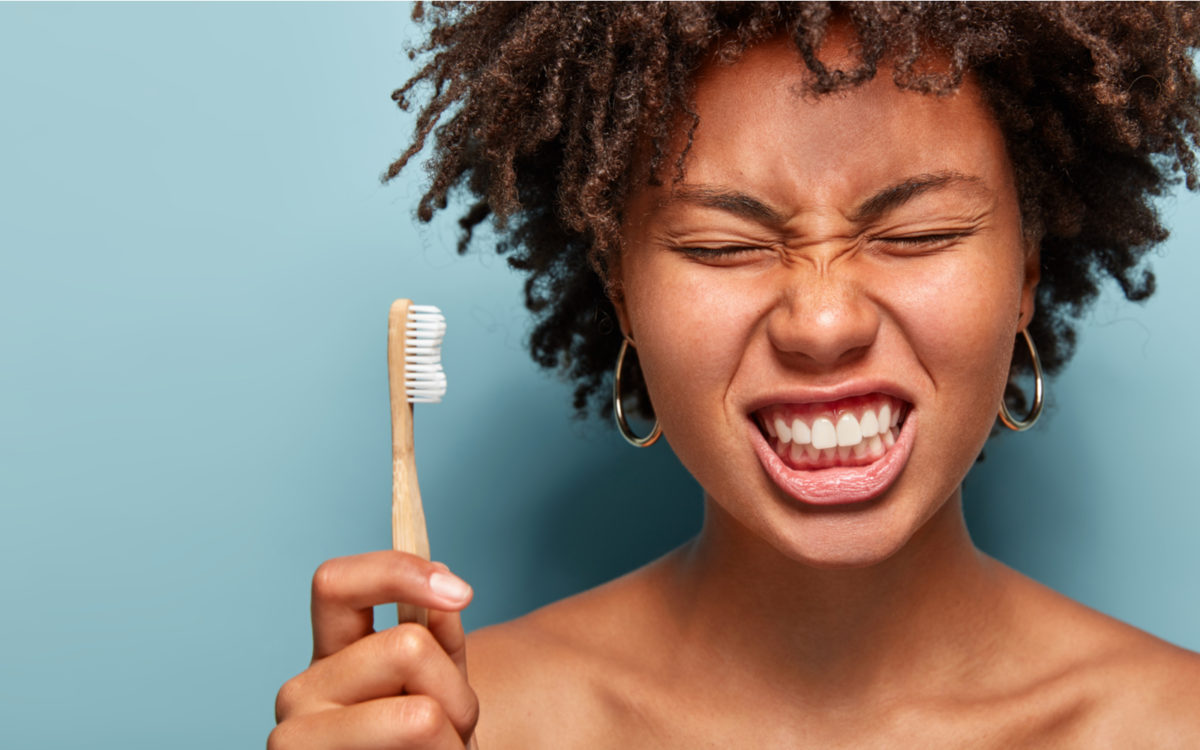 Woman holding toothbrush with a pained face