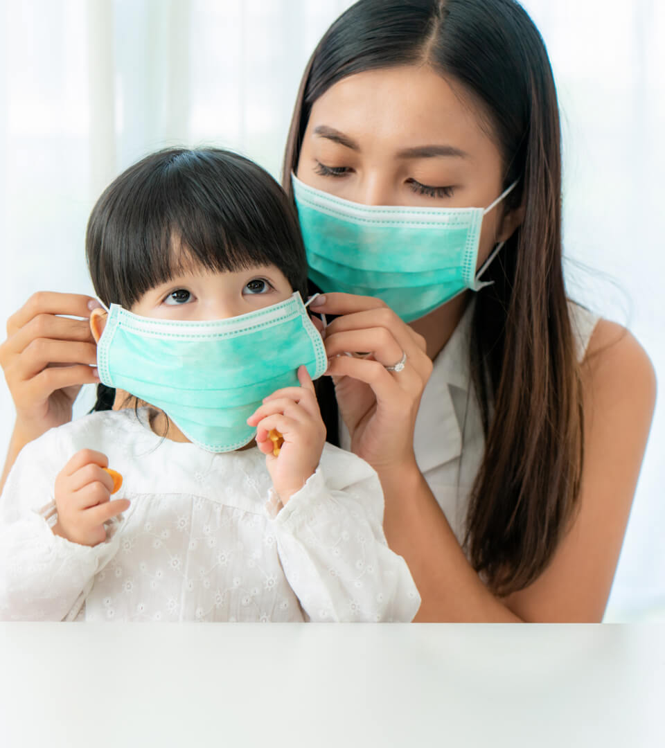 mother putting mask on her daughter's face